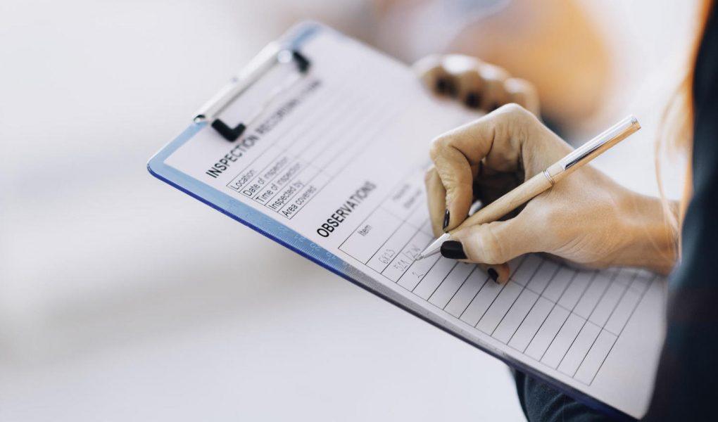 Facility management technician filling inspection form